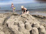 Børnene bygger sandslot ved stranden